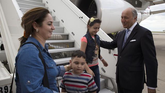 Le ministre des affaires étrangères Laurent Fabius accueille une quarantaine de réfugiés chrétiens irakiens à l'aéroport de Roissy Charles de Gaulle, le 21 août 2014 [Joel Saget / AFP]