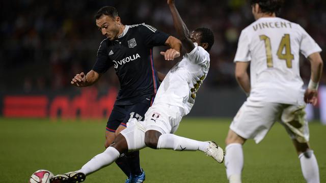 Le meneur de jeu de Lyon Steed Malbranque (g) est taclé par le Ghanéen Seidu Yahaya d'Astra en barrage aller de la Ligue Europa, le 21 août 2014 au stade de Gerland  [ / AFP/Archives]