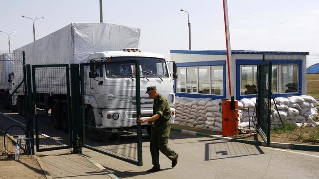 Un homme ouvre la grille du poste de douane au convoi de camions transportant de l'aide humanitaire le 22 août 20 à Izvarino à la frontière russo-ukrainienne [Sergey Venyavsky / AFP]