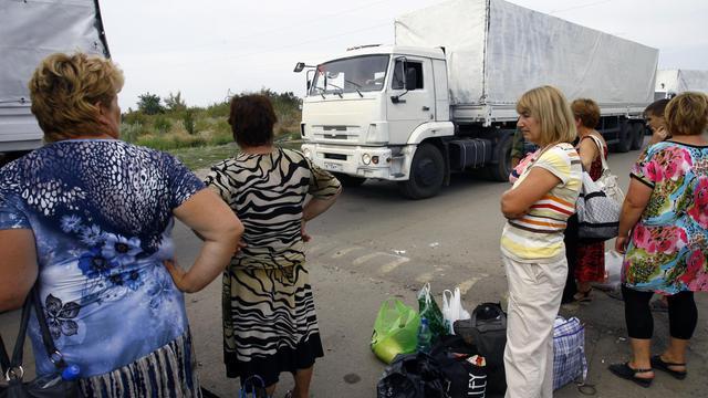 Des femmes observent les camions du convoi humanitaire envoyé par Moscou, au poste frontière d'Izvarino, entre la Russie et l'Ukraine, le 22 août 2014 [Sergey Venyavsky / AFP]