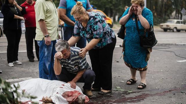 Le corps ensanglanté d'un homme tué lors de bombardements gît le 23 août 2014 dans une rue de Donetsk [Dimitar Dilkoff / AFP]