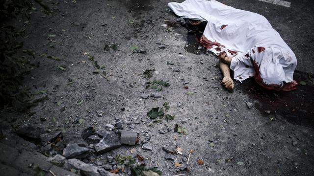 Le corps d'un homme ué le 23 août 2014 à Donetsk gît recouvert d'un drap  [Dimitar Dilkoff / AFP]
