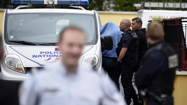 Un homme caché sous une couverture est amené dans une véhicule de police devant l'hôtel où trois personnes ont été retrouvées mortes le 28 août 2014 à Draveil [Martin Bureau / AFP]
