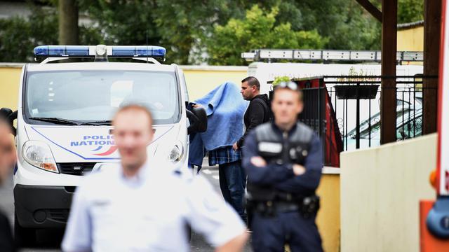 Un homme caché sous une est amené dans une véhicule de police devant l'hôtel où trois personnes ont été retrouvées mortes le 28 août 2014 à Draveil [Martin Bureau / AFP]