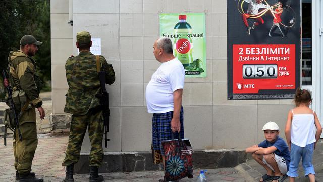 Des combattants prorusses placardent un manifeste à la population à Novoazovsk, le 29 août 2014 [Francisco Leong / AFP]