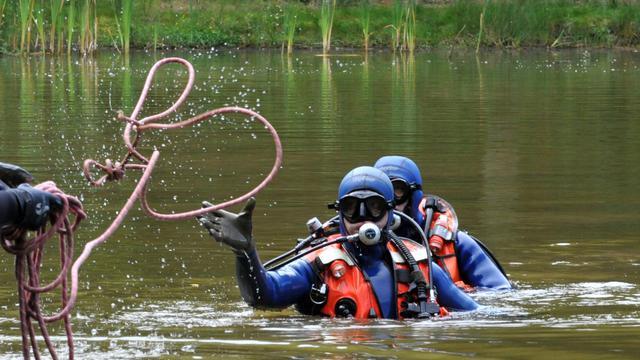 Des gendarmes sondent un étang à Chénérailles le 29 août 2014, à la recherche d'un bébé disparu [Thierry Zoccolan / AFP]