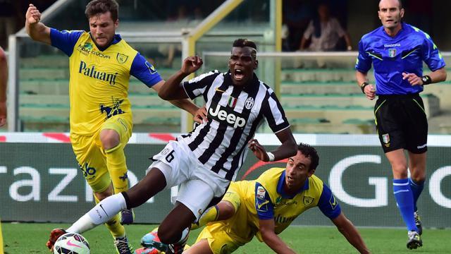 Le milieu français de la Juve Paul Labile Pogba est taclé par un défenseur du Chievo en ouverture du championnat italien, le 30 août 2014 au stade Bentegodi  à Vérone  [ / AFP]