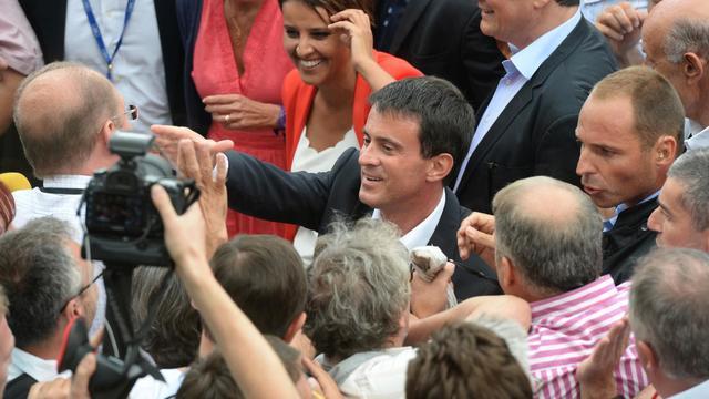Le Premier ministre Manuel Valls et la ministre de l'Education Najat Vallaud-Belkacem sont accueillis par des militants à l'université d'été à La Rochelle, le 30 août 2014 [Jean-Pierre Muller / AFP]