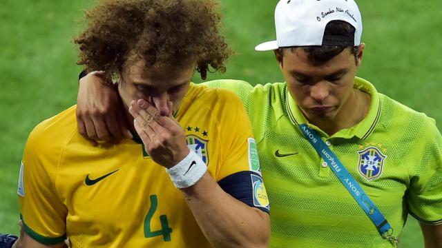 Le défenseur du Brésil David Luiz réconforté par son capitaine Thiago silva après l'humiliante défaite en demi-finale de la Coupe du Monde, 7 à 1 contre l'Allemagne au stade Mineirao, le 8 juillet 2014 à Belo Horizonte. [Gabriel Bouys / AFP/Archives]