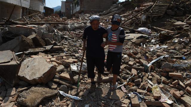 Une personne âgée, réchapée du séisme,  aidée par son petit fils dans les décombres à Longtoushan dans la province du Yunnan au sud-est de la Chine, le 7 août 2014  [Greg Baker / AFP]