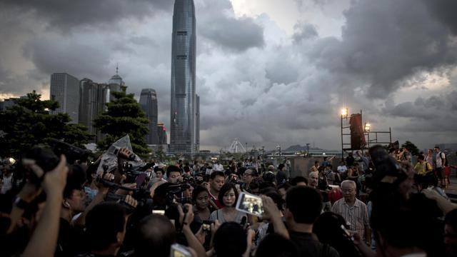 Benny Tai (d), co-fondateur du mouvement civil  Occupy Central parle à la presse, aux abords du siège du gouvernement de Hong Kong le 31 août 2014 [Alex Ogle / AFP]