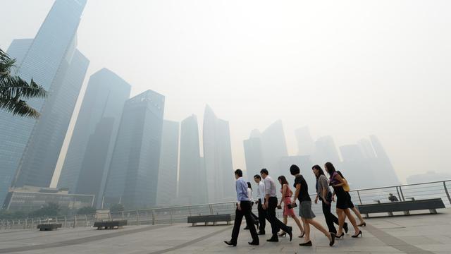 Des travailleurs se rendent à leur bureau, le 19 juin 2013 à Singapour [ROSLAN RAHMAN / AFP]
