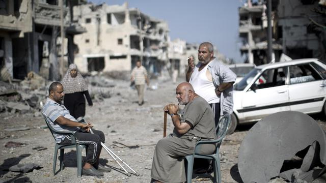 Des Palestiniens dans une rue dévastée de Gaza, le 1er août 2014  [Mahmud Hams / AFP]