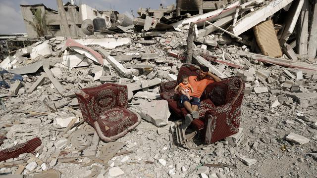Un Palestinien assis sur un sofa avec un enfant au milieu d'un champs de ruines à Al-Shejaea (banlieue de Gaza City), le 5 août 2014 [Mohammed  Abed / AFP]