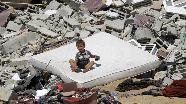 Un enfant palestinien sur un matelas parmi les ruines des habitations à Abasan, (sud de la bande de Gaza), le 7 août 2014 [Said Khatib / AFP]