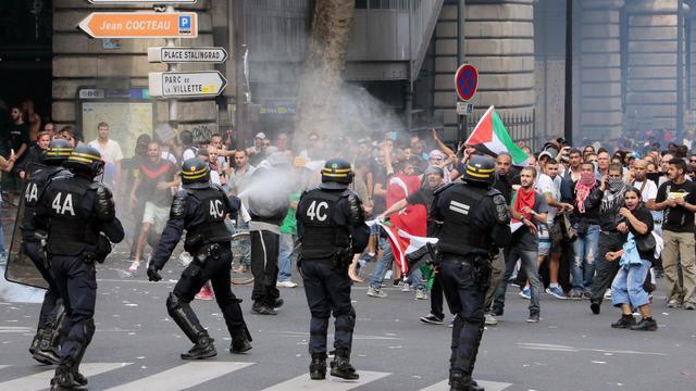 Des policiers diffusent des gaz lacrymogènes à Paris le 19 juillet 2014 [Jacques Demarthon / AFP]