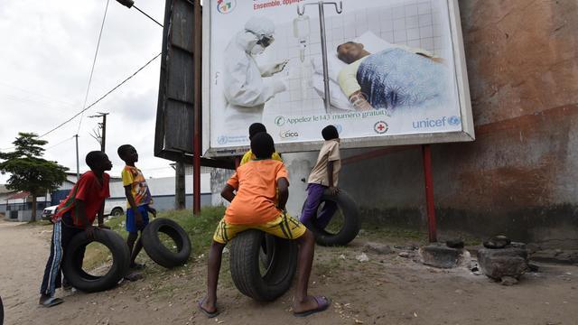 Des enfants regardent une affiche le 24 août 2014 mettant en garde contre le virus Ebola, à Abidjan [Sia Kambou / AFP]