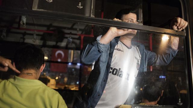 Un homme arrêté le 18 juin 2013 place Taksin à Istanbul emmené dans une voiture de police [Marco Longari / AFP Photo]