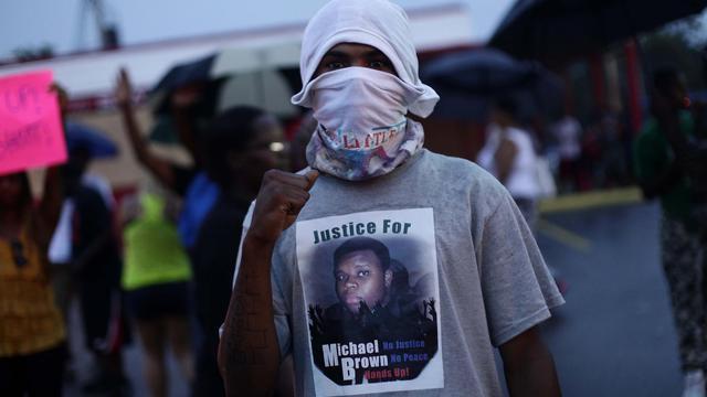 Un homme manifeste après la mort d'un jeune Noir tué par un policier, le 15 août 2014 à Ferguson dans le Missouri [Joshua Lott / AFP]