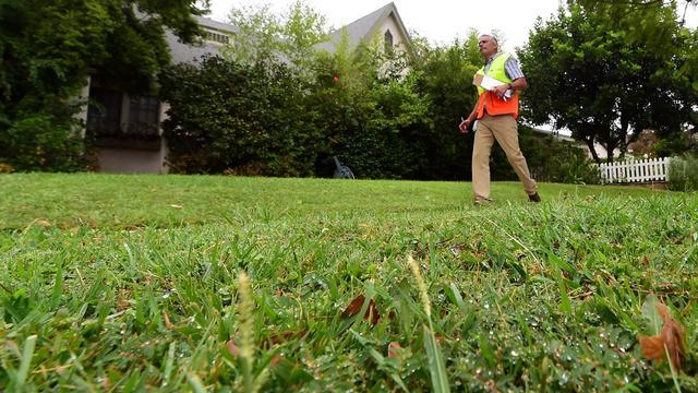 Enrique Silva patrouille à Los Angeles pour repérer les infractions à la réglementation sur l'usage de l'eau pour l'arrosage des pelouses, le 19 août 2014 [Frederic J. Brown / AFP]
