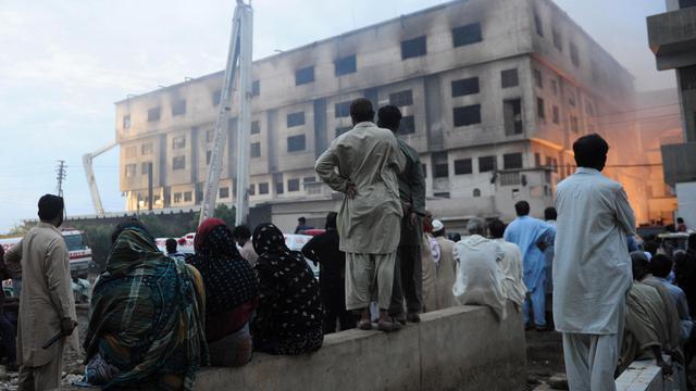 Des riverains observent les opérations de secours près d'une usine de textile incendiée de Karachi le 12 septembre 2012 [Asif Hassan / AFP/Archives]