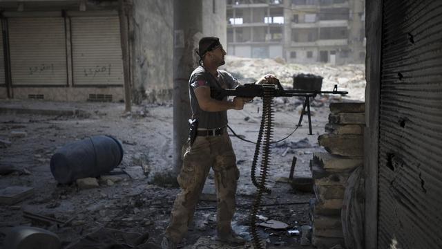 Un rebelle tire sur les forces gouvernementales dans un quartier d'Alep, le 26 septembre 2012 [Zac Baillie / AFP]