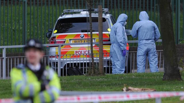 Des policiers près de l'endroit où un homme a été tué et deux suspects blessés dans l'est de Londres, le 22 mai 2013 [Carl Court / AFP]