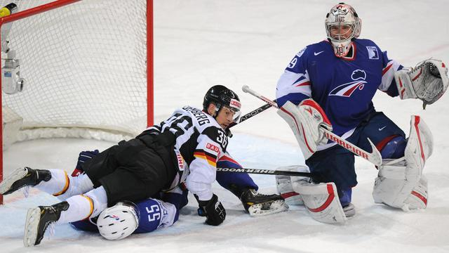 L'attaquant allemand Yannic Seidenberg chute sur le défenseur français Jonathan, devant le gardien tricolore Cristobal Huet, lors du Mondial-2017 de hockey sur glace, à Helsinki, le 14 mai 2013 [Alexander Nemenov / AFP]