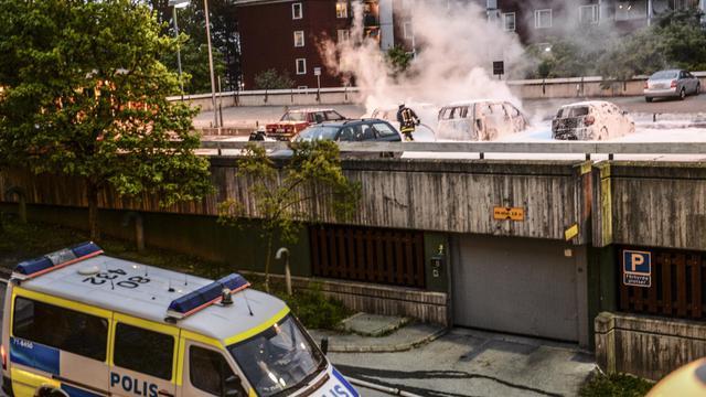 Des policiers tentent d'éteindre des voitures incendiées lors d'émeutes à Husby, au nord de Stockholm, le 20 mai 2013 [Fredrik Sandberg / Scanpix Sweden/AFP]