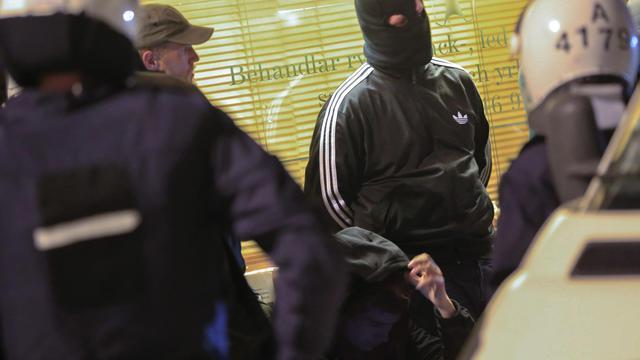 Des policiers fouillent un homme cagoulé le 25 mai 2013 à Stockholm [Fredrik Persson / AFP]