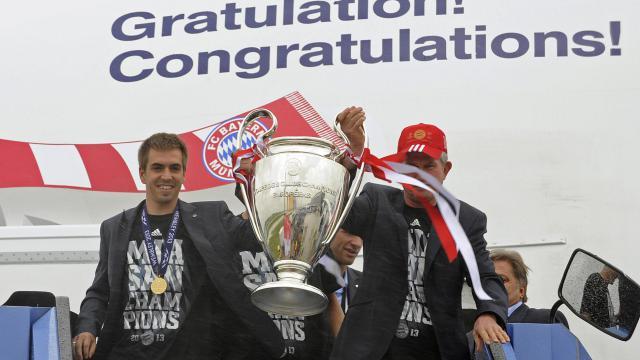 Le capitaine du Bayern Munich et l'entraîneur Jupp Heynckes descendent de l'avion avec le trophée de la Ligue des champions, le 26 mai 2013 à l'aéroport de Munich [Uwe Lein / AFP]