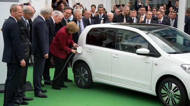 La chancelière Angela Merkel branche une voiture électrique, le 27 mai 2013 à Berlin, lors d'un congrès international sur l'électromobilité [Johannes Eisele / AFP]