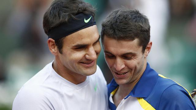 Le Suisse Roger Federer avec le Français Gilles Simon après le huitème de finale le 2 juin 2013 à Roland Garros à Paris [Martin Bureau / AFP]
