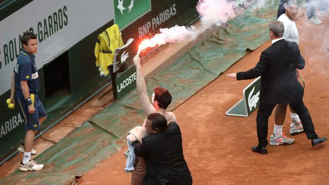 Le service de sécurité de Roland Garros évacue un homme opposé au mariage gay portant un fumigène lors de la finale opposant Rafael Nadal à David Ferrer le 9 juin 2013 à Paris [Martin Bureau / AFP]