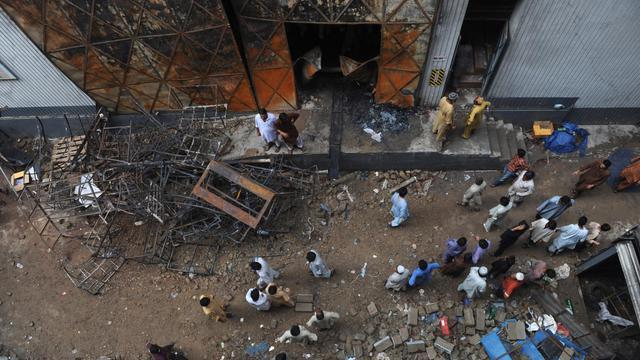 Des Pakistanais devant l'usine ravagée par un incendie, qui a tué au moins 289 ouviers, le 13 septembre 2012, à Karachi [Rizwan Tabassum / AFP]