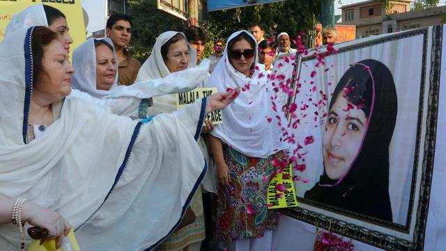 Des femmes lancent des pétales de rose sur le portrait de Malala Yusufzai, le 12 octobre 2012 à Peshawar [A. Majeed / AFP]