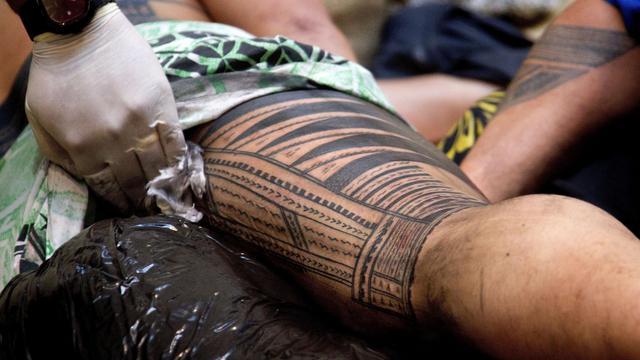 La jambe de Ricky Masoe est travaillée par le maître tatoueur Su'a Paul Sulu'ape lors d'une démonstration de tatouage traditionnel, le 5 septembre 2012 à Wellington, en Nouvelle-Zélande [Marty Melville / AFP/Archives]