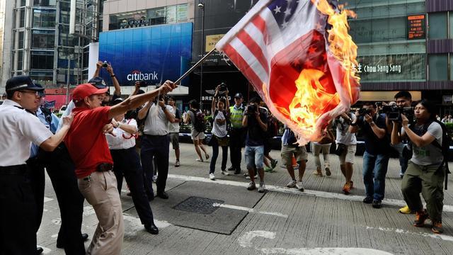 Un manifestant brûle un drapeau Etats-Unis/Japon, lors de protestations contre l'achat d'îles par le Japon, le 16 septembre 2012 à Hong Kong [Antony Dickson / AFP]