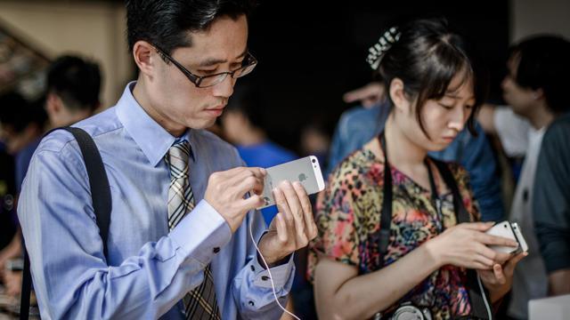 Des clients inspectent le nouvel iPhone 5, le 21 septembre 2012 dans une boutique Apple à Hong Kong [Philippe Lopez / AFP]