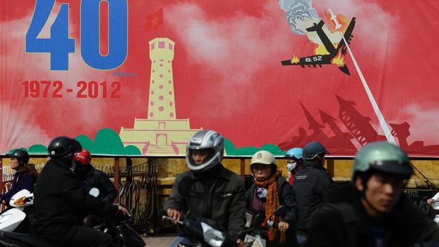 Des motocyclistes passent devant une affiche commémorant les bombardements de Hanoï en 1972, le 21 décembre 2012 [Hoang Dinh Nam / AFP]