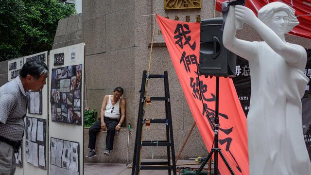 Un homme regarde des photos le 3 juin 2013 à Hong Kong avant une veillée aux flambeaux prévue pour le 24e anniversaire de la répression de Tiananmen [Philippe Lopez / AFP]