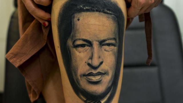 Une femme montre sa jambe sur laquelle est tatoué le visage de l'ancien président Hugo Chavez, le 12 avril 2013 [Luis Acosta / AFP]