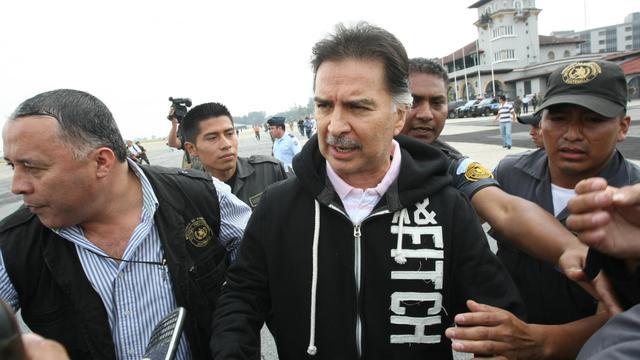 L'ex-président guatémaltèque Alfonso Portillo (c) est escorté avant de s'envoller pour les Etats-Unis, le 24 mai 2013 à Guatemala [ / AFP/Archives]