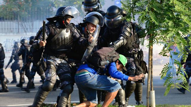 Des policiers anti-émeutes interpellent un manifestant le 16 juin 2013 devant le Macarana à Rio [Tasso Marcelo / AFP]