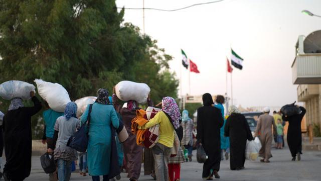 Face aux bombardements de l'aviation gouvernementale syrienne, des centaines de réfugiés syriens se pressent à la frontière turque, les bras chargés des quelques sacs de vêtements et cartons de nourriture qu'ils ont pu sauver.[AFP]