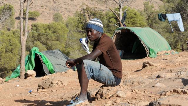Un migrant africain se repose dans le camp de la petite forêt de Sidi Mâafa, à Oujda, le 10 septembre 2012 [Abdelhak Senna / AFP]
