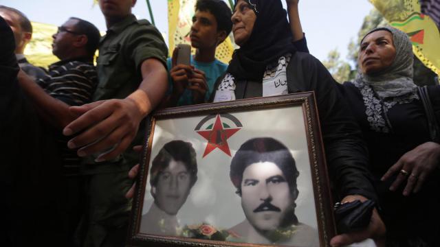 Des réfugiés palestiniens montrent des photos de leurs proches disparus lors du massacre de Sabra et Chatila, à Beyrouth, le 18 septembre 2012 [Joseph Eid / AFP]