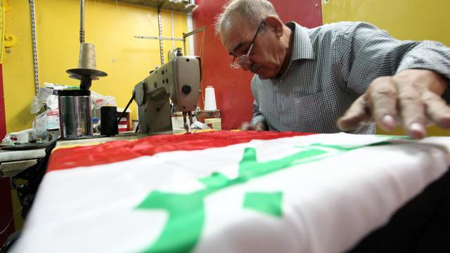 Un tailleur irakien coud un drapeau national dans son atelier à Bagdad, le 20 septembre 2012 [Sabah Arar / AFP]