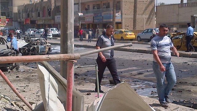Des Irakiens marchent dans le quartier de Karrada dans le centre de Bagdad, cible d'un attentat à la bombe, le 30 septembre 2012 [W.G. Dunlop / AFP]