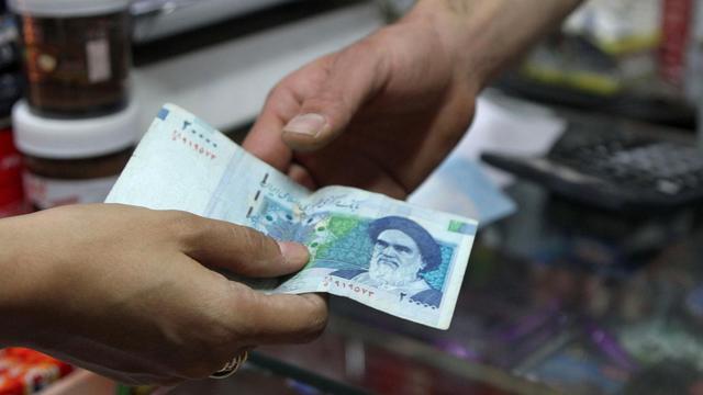 Une personne paye avec un billet de 20.000 rials, le 30 septembre 2012 à Téhéran [Atta Kenare / AFP]